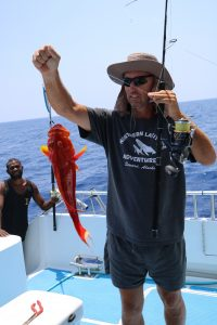 Garry, (wearing hat made by mum) jigs a coral trout